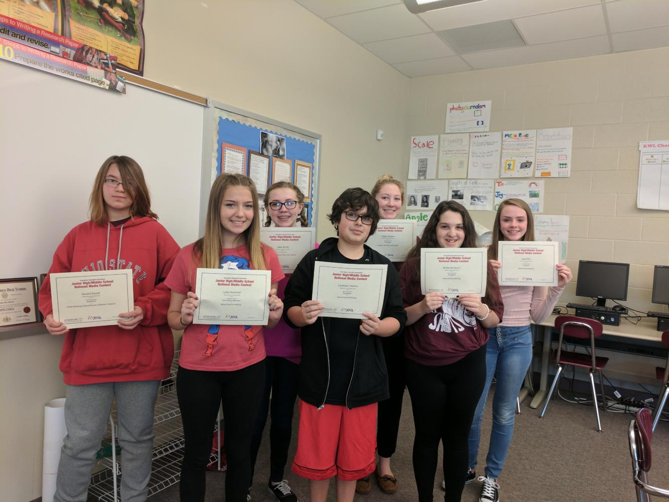 Aurora Soural, Lydia Newman, Jolee Smith, Cameron Havens, Paige Glasgow, Mckenzie Quirin and Julia Pitts display certificates recognizing their ratings for the National Media Contest. (pictured from left to right)