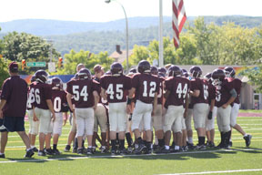 The seventh grade white football team gets into their huddle before the game against Bishop Guilfoyle on Oct. 2.