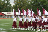 The seventh grade marching band marches off the field after their pre-game performa