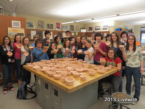Community Inspired Arts club members stand together holding the bowls they made for the empty bowls program. ~Photo by Ann Bickel