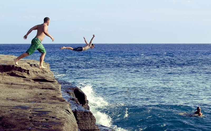 A man jumps off of a Cliff in Honolulu, Hawaii. 