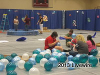 Students sit on the ground to blow up the social balloons. Photo by Emily Glacken