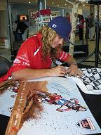 Ashley Fiolek signs photographs of herself as she represents her Honda Racing team. Photo courtesy of Gerald Geronimo.