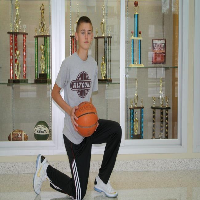 Nic+Urchick%2C+eighth+grade%2C+%22takes+a+knee%22+in+the+front+of+the+many+basketball+trophies.