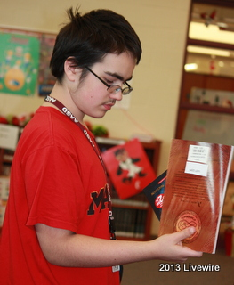 Ninth grader, Kyle Roberts examines the books that he is purchasing at the Book Fair. He bought the books to support Scholastic. Photo By: Hanna Feathers