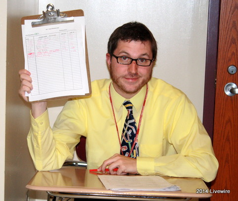 Ninth grade Civics teacher, John Blough, holds up the sheet for the boys bathroom. Teachers who are assigned a certain time to sit outside the bathroom to do the sign in and out sheet. Photo by Hannah Barr
