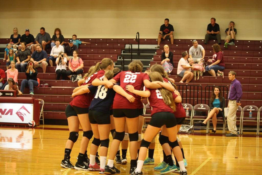 The team huddling together. As the lady spikers go against their rival Hollidaysburgh, they talk about what they need to do to win the game. Photo by Kizzy Thompkins