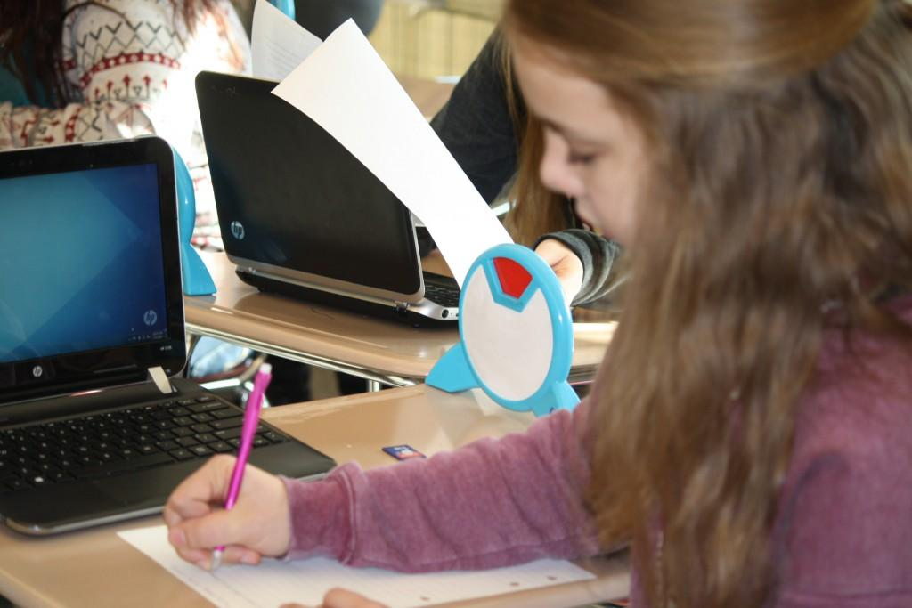 Ninth grader, Anna DeRubeis, works on her assignments in newspaper class Photo taken by Sarah Harmon