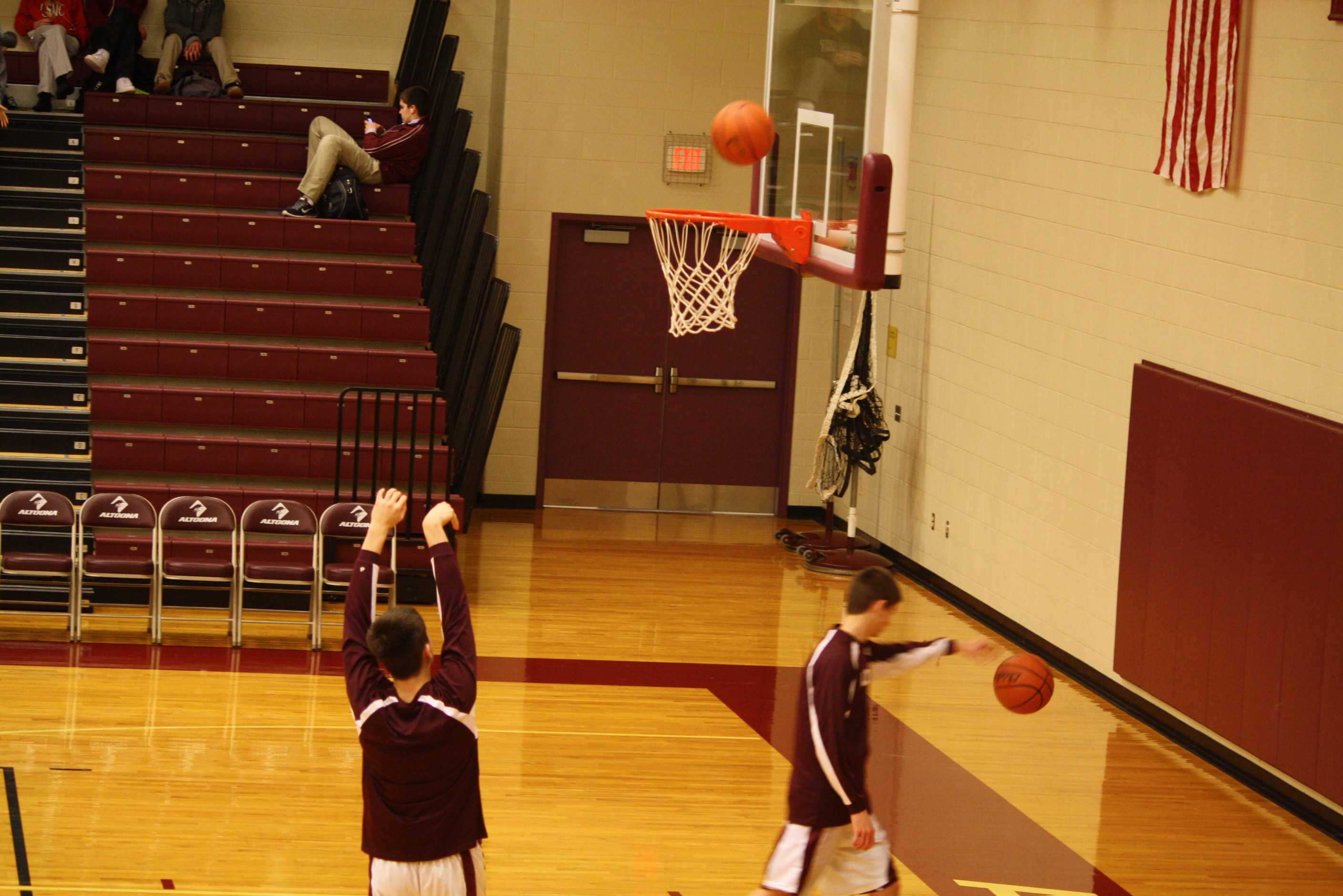 Ninth grader, Max Sankey warms up with some free throws before their basketball game  Photo taken by: Emily Simmons