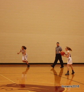 To the hoop! Seventh grader Emma Skelley runs the ball down the court to shoot a three pointer. Skelley plays on the seventh grade white girls' basketball team but gets playing time for the eighth grade basketball team.