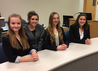 Jazzmine McCauley, Karlie Thompson, Raquel Dunio, and Caroline Danison sitting at the table waiting for the trial to begin.
