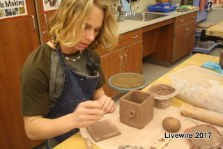Get sculpting! Ninth grade student Jace Greene is working on the top to his project. His project was a clay box with a face on the front.