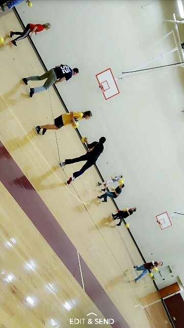 Students play dodge ball in the gym with gym teachers and other students.