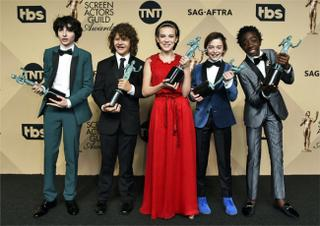 Finn Wolfhard, from left, Gaten Matarazzo, Millie Bobby Brown, Noah Schnapp, and Caleb McLaughlin pose in the press room with the awards for outstanding performance by an ensemble in a drama series for