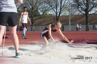 Freshman Anna Rupp jumps into the sand pit during the long jump event. Long jump is an event that can be competed by both men and women.