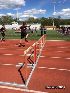 You can do it! An eighth grader competing in the 100m hurdles finishes his last hurdle. It is essential to get the steps right when taking off for hurdles.