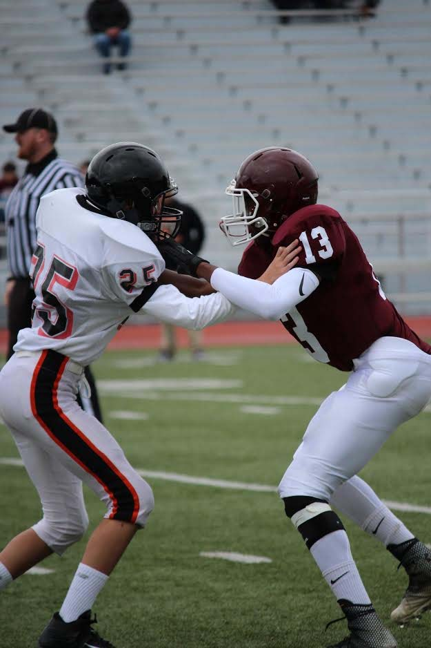 Altoona Mt. Lion Edwin Franklin defends against Latrobe player number thirty five. Altoona won with a schore of 39-12 on September second.