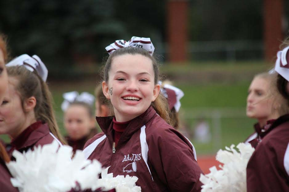 Ninth grader Elizabeth Frank smiles and cheers for AAJHS on Septemeber second. She cheered at the game against Altoona Mt. Lions and Latrobe.