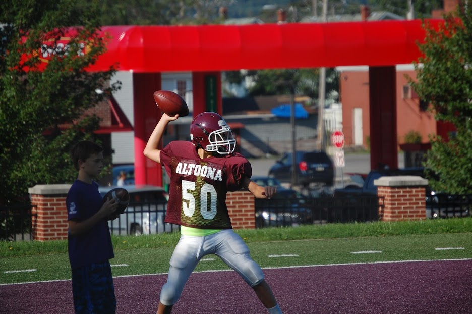 %2350%2C+a+seventh+grader+on+the+maroon+football+team+throws+a+ball+to+his+team+mate+on+September+3rd%2C+2017.+After+%2350+practiced+throwing+the+ball+to+his+team+mates+everyone+took+a+break+and+started+to+practice+plays.+