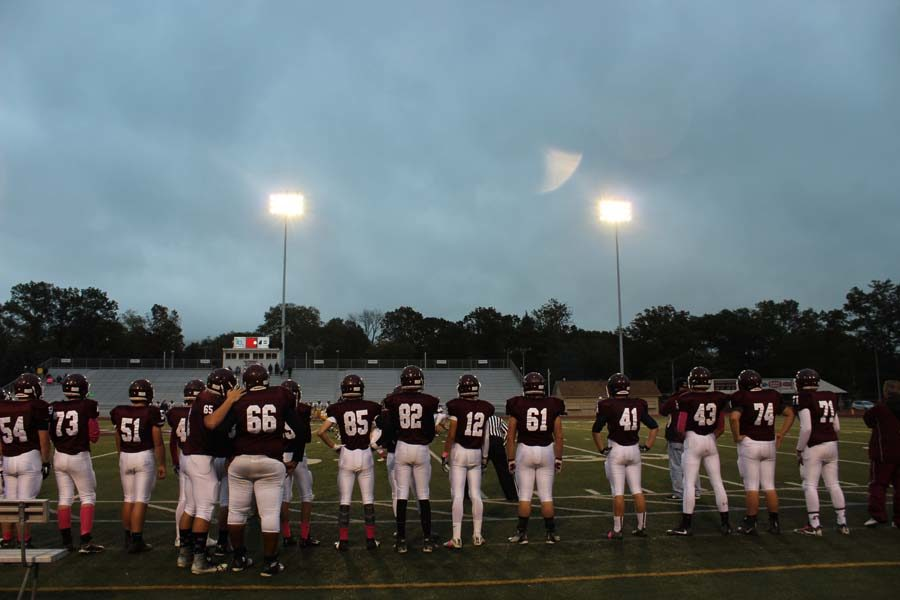 9th grade football players watch from the sidelines as the mountain lions starting line up started the game. Photo by:Jocelyn Fetter