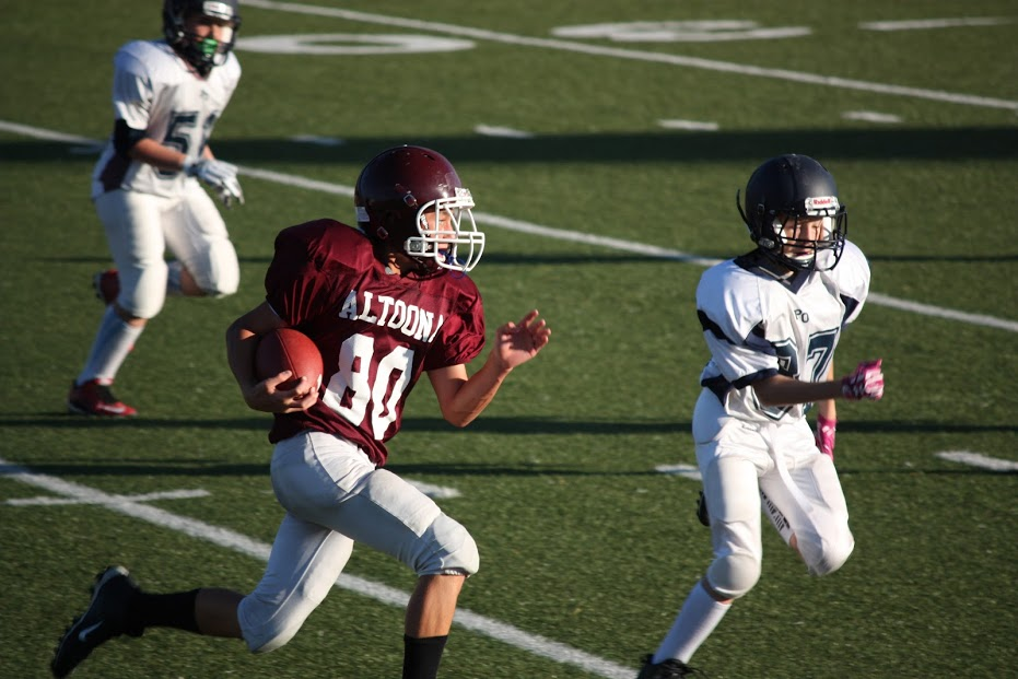 Ryan Hopkins running with the ball at his football game on October 10th, 2017. Hopkins ran with the ball, but got tackled soon after by a member of the opposite team.