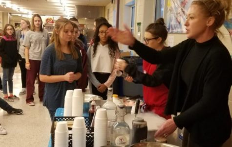 Students of team one gather around to watch the ice cream being made.