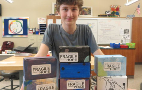 Love! Ninth grader Michael Herren stands behind peace boxes in Mrs.O'Roarks art class room.