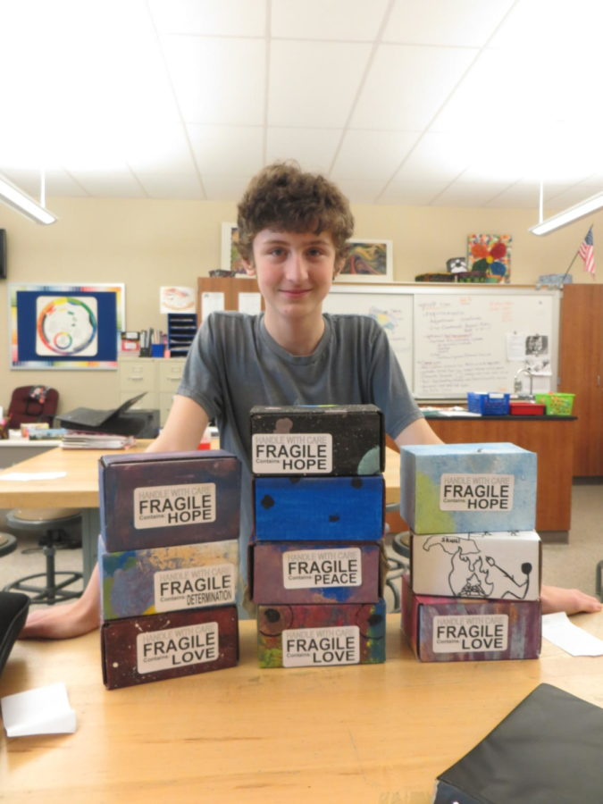 Love! Ninth grader Michael Herren stands behind peace boxes in Mrs.ORoarks art class room.