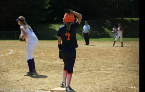 Riley Steinbugl waits on base while the pitcher throws the ball. She is getting ready to take a lead.