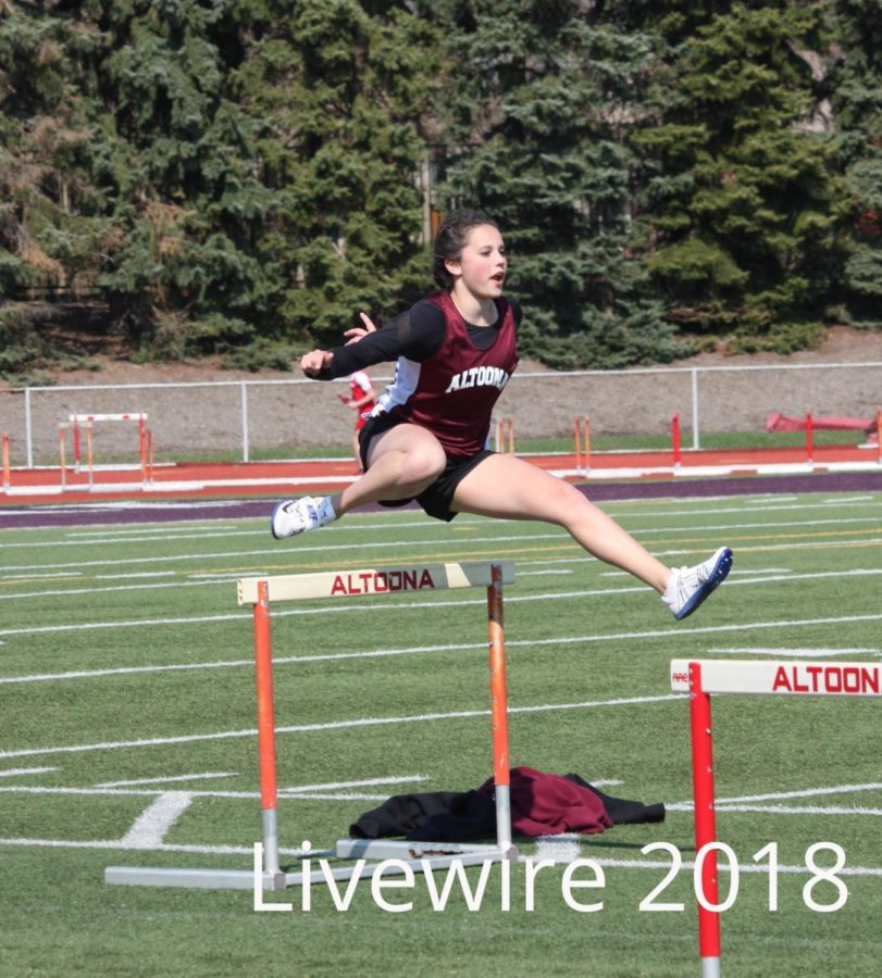 Hurdle%21+Niya+Perez+practices+jumping+over+hurdles+at+the+girls+track+meet.+Perez+practiced+then+went+to+her+other+events.