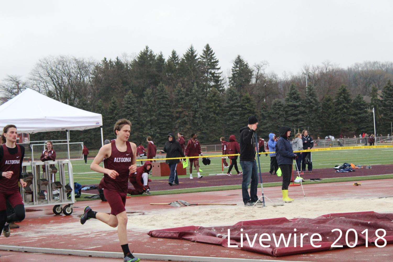 Rush. Andrew Carini runs the 1600 meter dash at the track meet on April 3. Carini ran then waited for his next event.
