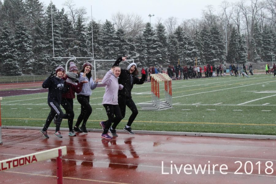 Peace.+Girls+run+and+smile+at+track+practice+on+April+9.+The+girls+ran+then+warmed+up+on+the+field.
