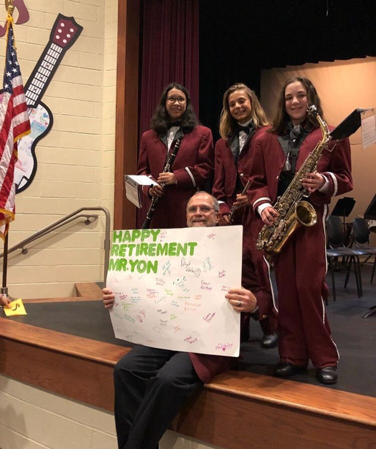 Mr. Yon and the seventh graders. Mr. Yon holds up his retirement poster with seventh graders from the J.V. concert and marching band.