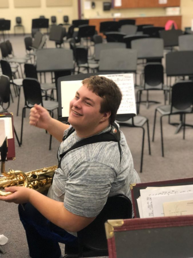 I'm ready! Aiden Phillips chats with his friends before practicing songs for county band with his baritone saxophone.