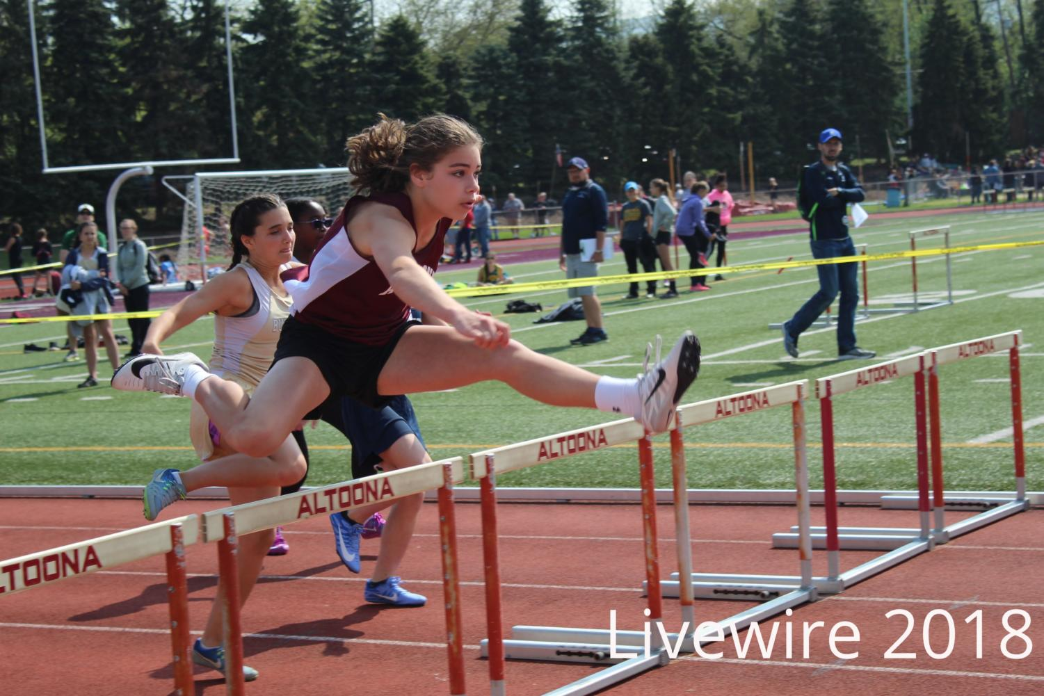 Hurdle. Gwyenth Rentz jumps over a hurdle at the track meet on May 12. Rentz jumped and then recorded her time.