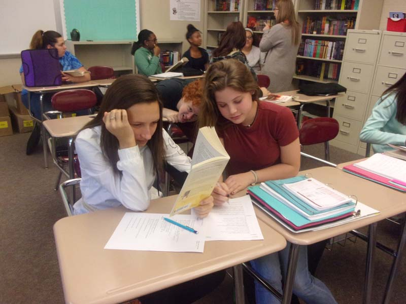 With+their+minds+focused%2C+Kelcie+Kenney+and+Ashlee+Moyer+work+on+their+comprehension+questions+in+Michelle+Garman%27s+English+class.++Students+worked+on+their+homework+before+class+ended.