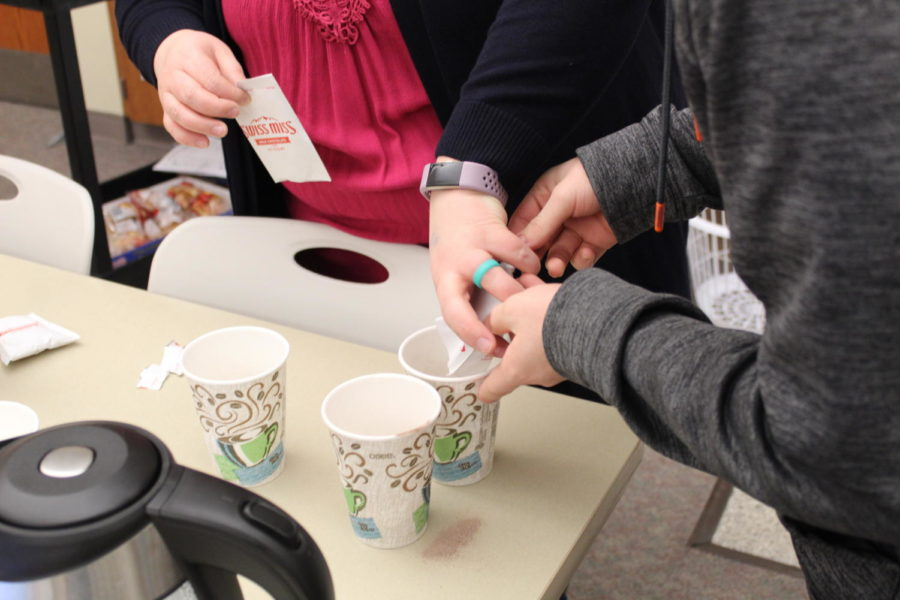 Helping hands. Amy Arthur is helping Milton Hillard pour powdered hot chocolate in the cups. She was a big help with the students.