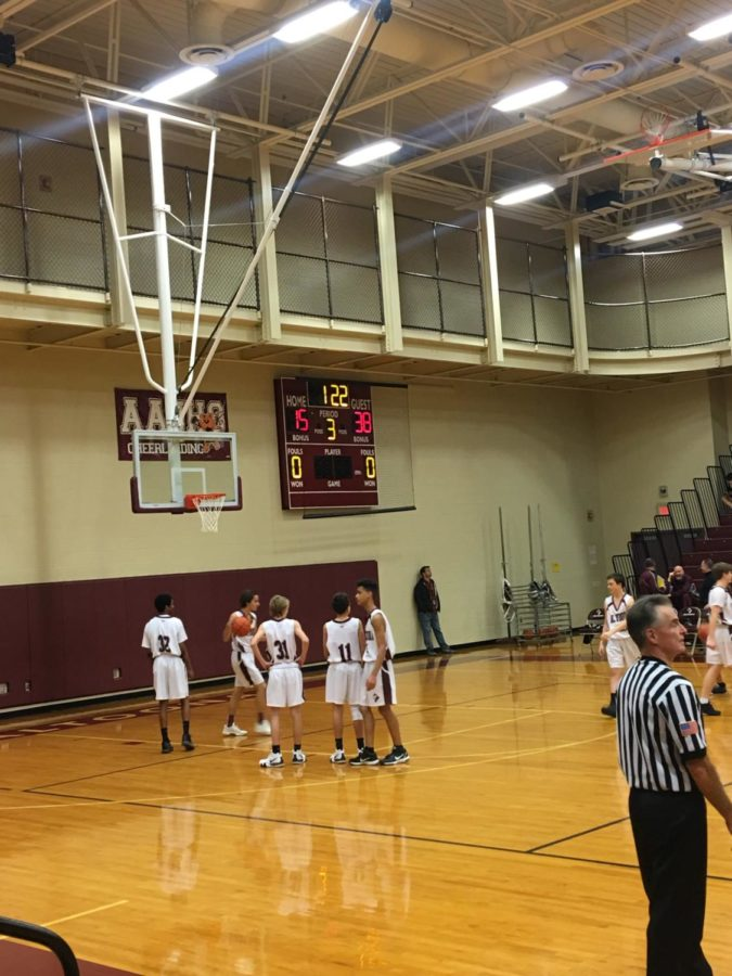 The ninth grade maroon boys' basketball is warming up before the third period.  They already finished two hard periods.