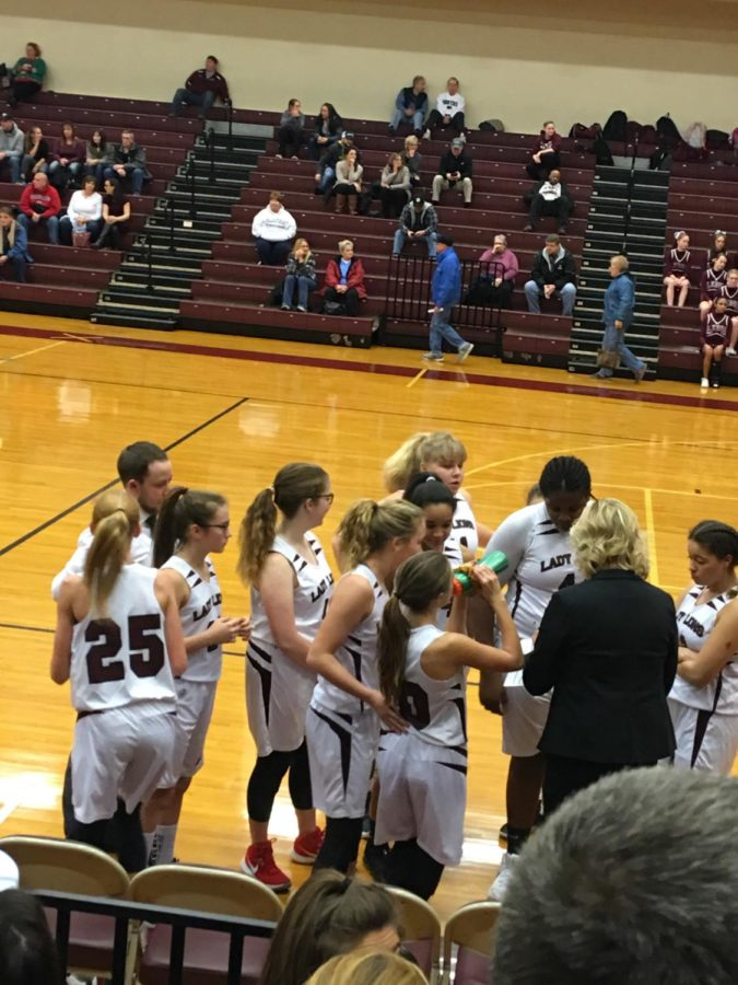 Eighth grade white girls' basketball team takes a huddle before the second period starts.  The white team had a very successful game.