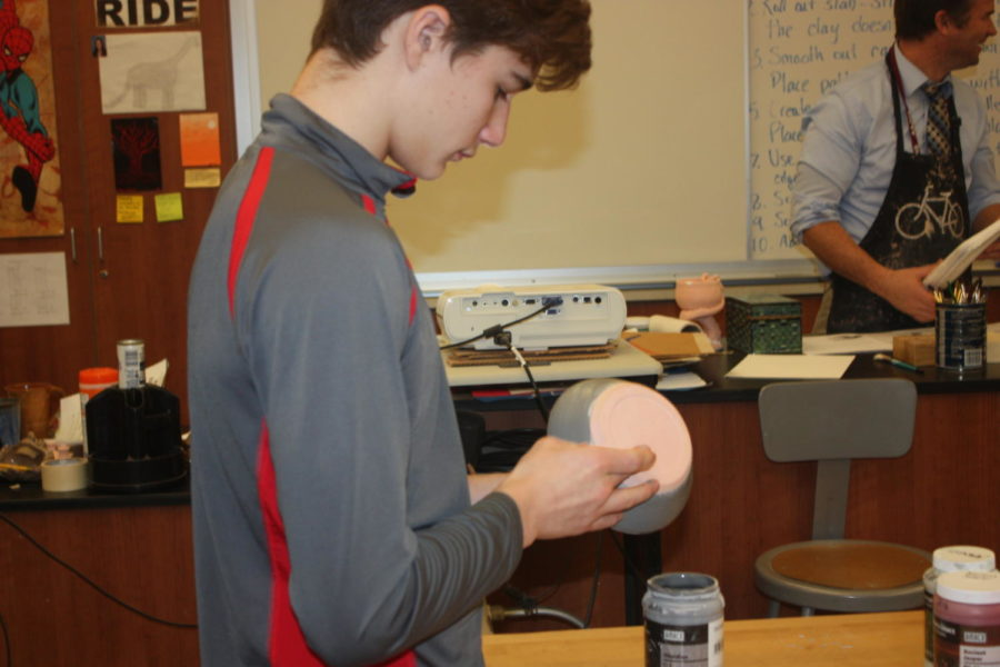 Clean it up!  Isaac Kratzer cleans out the edges of his paint.  He made a bowl out of clay and is close to finishing.