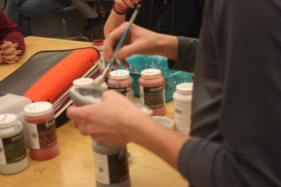 Paint it up! Isaac Kratzer paints his bowl the color grey.  He has already painted one coat and had to paint a second.