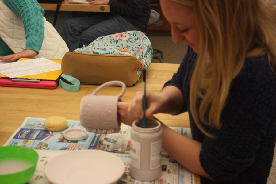 Finishing touches!  Evelyn Stroup puts some finishing touches on her mug.  She painted it a light pink color.