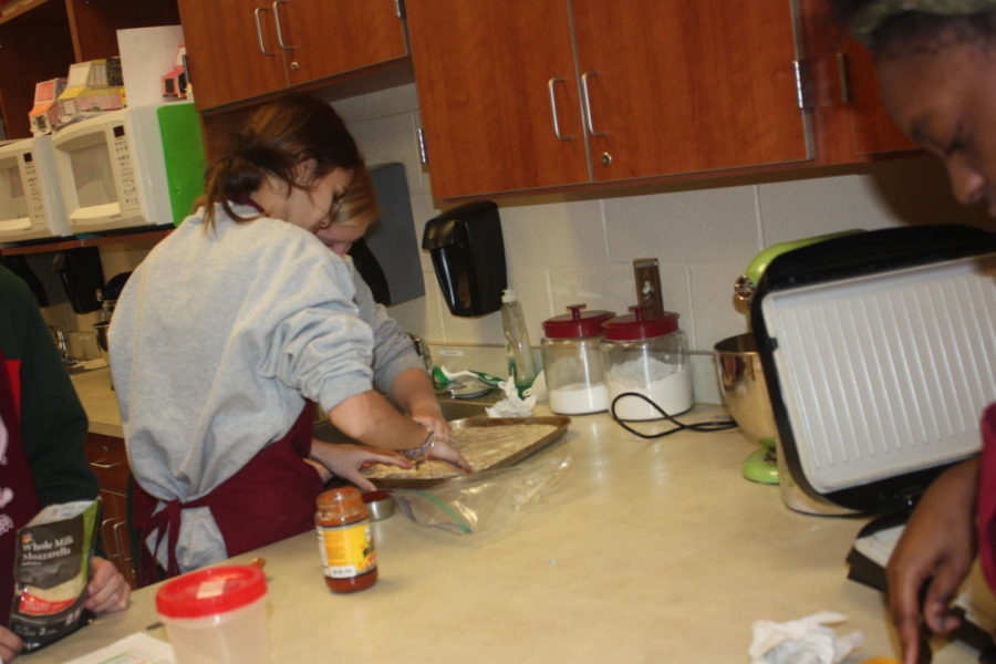 Team work! Rebecca Dull and Jaci Clouser work together to spread the pizza dough out evenly.  Dull then added the pizza sauce to the dough