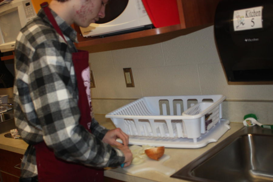 Slice it thin! Andreas Pentsas works on slicing the onion for his phillycheese steak. Everyone is foods had to make a food truck before the end of the semester.