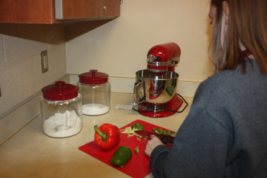 Dice it up!  Hailey Singer cuts up green and red peppers. Singer's group is made philly cheese steaks.