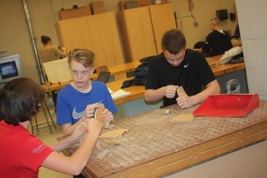 Make it smooth! Alexander Yost, Aiden Everhart and Jaxson Ferguson use the small table to sand.  They sanded the side piece to their project.