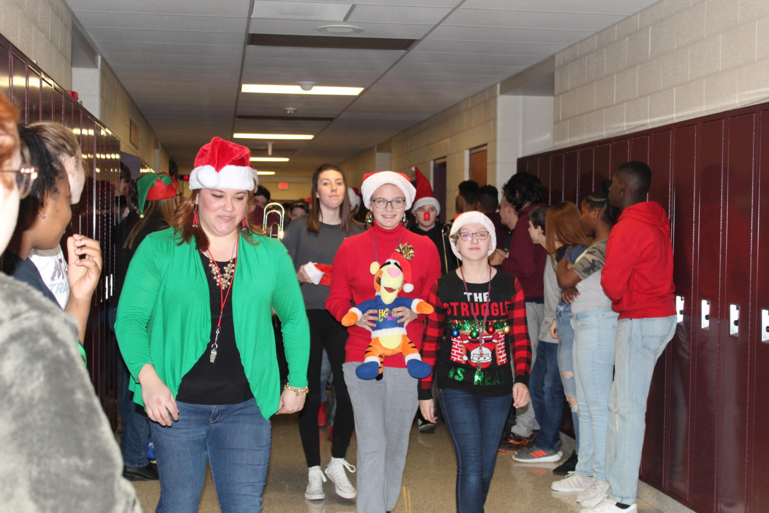 Ugly Sweater Weather Teachers and faculty dress festive for the AAJHS Christmas parade. These teachers lead the speech team in the parade.