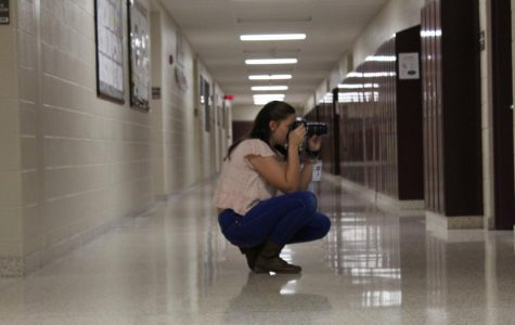 Student reporter Danielle Bardelang takes photographs for an upcoming story on Livewire. Junior high news reporters take photos and write stories for the school's newspaper.