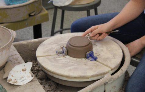 Ninth grader Emma Chirdon uses wheel in pottery class. The pottery class made mugs for the roar mug grant program.