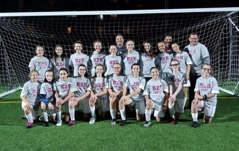 The girls' soccer team gathers with their coaches for a photo after another win is added to their undefeated streak. The past season for the girls' soccer team added their fourth undefeated season to their streak as they win against opposing teams.